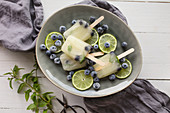 Blueberry mojito cocktail ice lollies in a dish