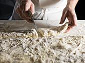A baker portioning ciabatta bread dough