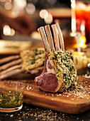 A raw rack of lamb with a herb crust on a chopping board