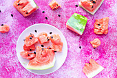 Watermelon slices on a white plate on a pink surface