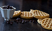A white bowl with chocolate chips and a stack of homemade waffles