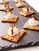 Crackers with cream cheese, crickets and mealworms