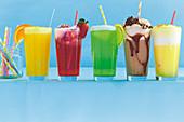 Verschiedene alkoholfreie Cocktails in Gläsern vor blauem Hintergrund