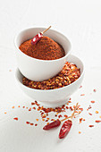 Chilli powder and chilli flakes in white bowls