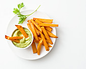 Oven-baked spicy sweet potato chips with avocado cream