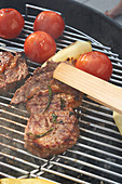 Beef steaks, tomatoes and hot peppers on a grill