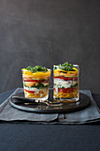 Layered salads with vegetables and melon in glasses