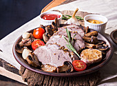 Slices of baked roasted meat. Cold-boiled pork with mushrooms, garlic and cherry tomato on brown plate