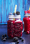 Summer smoothies of blackberries, blueberries, red and black currant, raspberries in glasses on blue background
