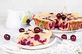Sweet cherry clafouti and piece of cake on wihite saucer