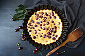 Sweet cherry clafouti cake on cake pan over on dark background with fresh cherry