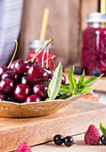 Fresh sweet cherries with drops of water on plate over wooden table