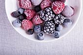 Frozen berries in frost (raspberries, blackberries, blueberries) on white plate