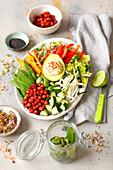 Vegane Buddha Bowl mit Hummus, Avocado, Süsskartoffeln, gebackenen Kichererbsen und Gemüse