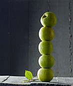 Green apples stacked in a tower