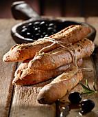 Olivenbaguette imit Schnur umwickelt und schwarze Oliven