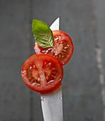 Tomatenscheiben mit Basilikumblatt auf Messerspitze mit Wassertropfen