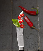 Red chilli rings on a knife tip with water droplets