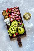 Blauschimmelkäse, Brot, Obst auf Schneidebrett, daneben ein Glas Weisswein