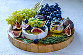 Camembert cheese with figs, honey, grapes and fragrant herbs on a cutting board