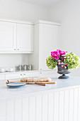 Brot und Blumenstrauß in heller Landhausküche