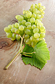 Green grapes on a wooden background with vine leaves