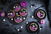 Blackberry yoghurt tartlets with mint leaves and meringue drops on black plates