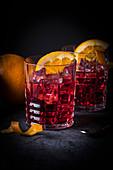 Italienischer Cocktail-Klassiker Negroni auf Eis mit Orangen im Glas