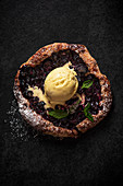 Blueberry galette with ice cream on a black slate