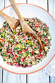Large bowl of Lebanese tabbouleh salad with bulgur wheat, tomatoes, cucumber, onion, pomegranate