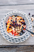 Vegan muesli with coconut yoghurt, cranberries, strawberries, blood oranges and blueberries