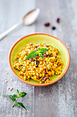 A salad with pearl couscous, chickpeas, carrots, curry cream and cranberries