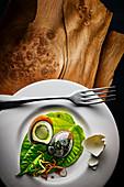 Food-Art: Tausendjähriges Ei (Spezialität aus China), Teller auf Holzuntergrund