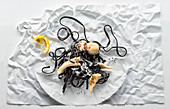 Food art: black linguine with octopus on creased paper