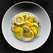 Lemons and limes with black sesame seeds and foam