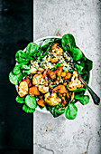Grain bowl with roasted cauliflower, pumpkin, and chickpeas over lettuce