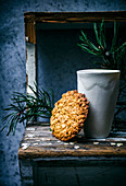 Thin honey and oat cookie with greenery and ceramic cup