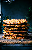 Thin honey and oat cookies stacked with greenery