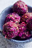Vegane Energy Balls mit Datteln, Kakao, Cashew und Rosenblättern (Nahaufnahme)