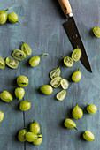 Gooseberries being chopped on a blue background