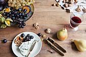 Blauschimmelkäse mit Trauben und Nüssen serviert mit Rotwein auf rustikalem Holztisch