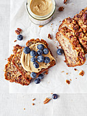 Loaf of banana bread with nut butter and blueberries