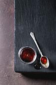 Homemade liquid transparent brown sugar caramel in glass jar standing on black wooden board