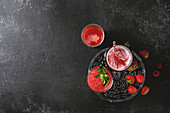 Drei verschiedene rote Fruchtsmoothies mit Erdbeere, Wassermelone und Granatapfel