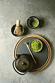 Ingredients for making matcha drink. Green tea matcha powder in ceramic bowl, traditional bamboo spoon and whisk on slate board, black iron teapot over grey texture background