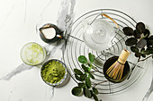 Ingredients for making matcha ice drink. Green tea matcha powder in ceramic bowl, traditional bamboo spoon, whisk on cooling rack, glass teapot, ice cubes