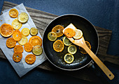 Slices of candied orange and lemon in a pan with syrup being lifted out with a wooden spatula to cool on baking paper