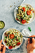 A woman eating vegan pasta salad from a ceramic handmade plate and a small bowl of avocado dressing accompany