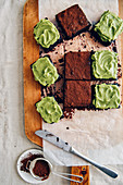 Avocado brownies some of which are topped with avocado frosting and the rest of which are topped with cocoa powder