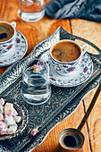 Turkish coffee served in a traditional Turkish coffee cup in a copper tray, a glass of water with a rose petal and Turkish delights on the side